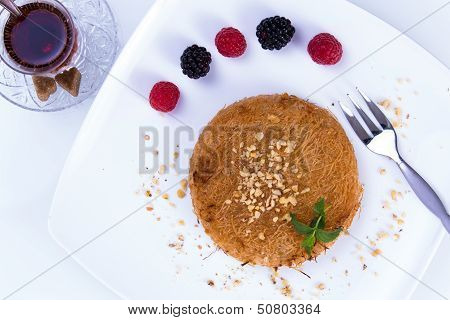 Turkish dessert kunefe served on a white plate with mint leaves and sliced strawberry along red and black berries poster