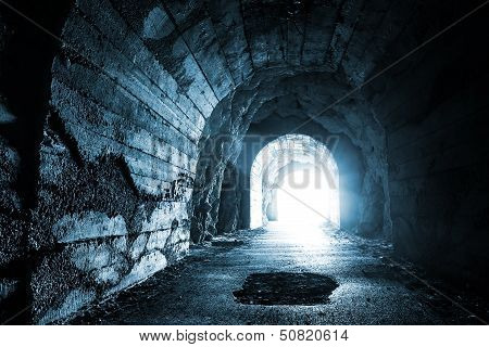 Glowing exit from dark abandoned tunnel. Monochrome blue photo poster