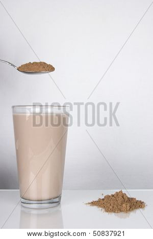 Chocolate Milk And Spoon With Powder