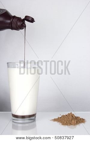 Chocolate Syrup Pouring Into Glass Of Milk