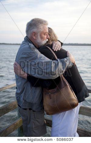 Older Couple Hugging On Dock