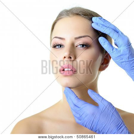 Beauty treatment of the young beautiful female face, doctor's hand in gloves touch face of beautiful young woman isolated on white