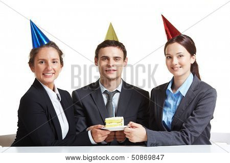 Portrait of young business partners in birthday caps holding piece of cake on saucer and looking at camera