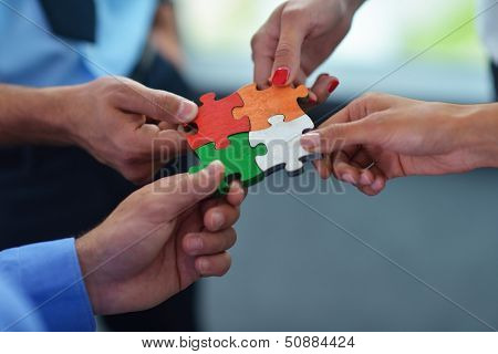 Grupo de pessoas de negócios, montar quebra-cabeças e conceito de ajuda e apoio de equipe representam