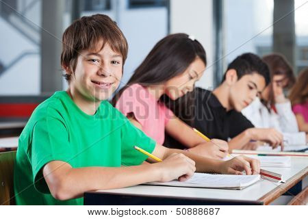 Portrait of happy teenage boy sitting at desk with friends writing in classroom