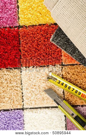 Carpet swatches, knife and tape measure