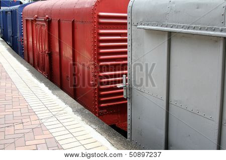 Gray, Red, Blue Train Bogies at the train station