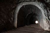 Dark abandoned tunnel interior perspective with glowing end poster