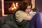 Red hair teenager girl fondling cat at home sitting by fireplace. poster