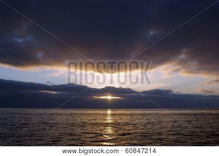 An Ocean Sunrise Peeking Through The Clouds
