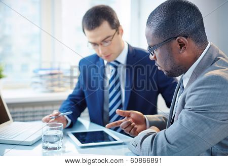 Image of two young businessmen discussing data in touchpad at meeting