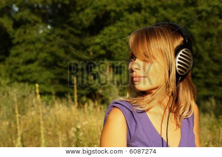 Girl walking and listening to music in the open