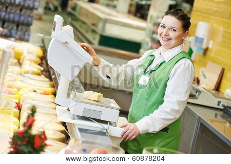Smiling saleswoman assistant in supermarket working with scales balance to pregnant female customer during shopping at store