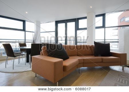 open plan living room with an orange sofa and floor to ceiling windows