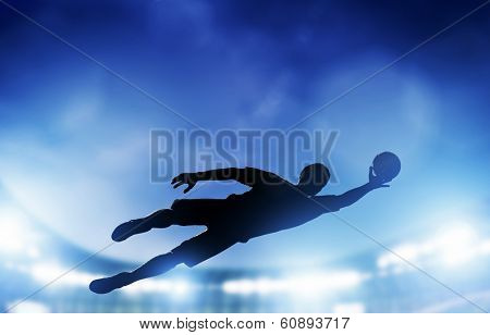 Football, soccer match. A goalkeeper jumping to defend, save the ball from goal. Lights on the stadium at night.