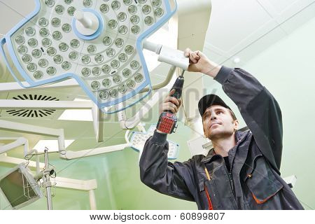 Carpenter joiner with screwdriver mounting equipment at surgery room in clinic