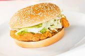 Crispy chicken burger on a white plate close up poster