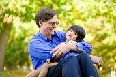Businessman holding his disabled son on grass. Child has cerebral palsy. poster