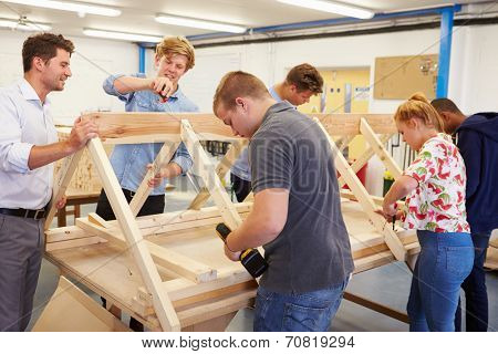 Teacher Helping College Students Studying Carpentry