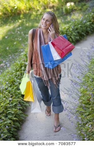 Young Woman With Shopping Bags And Cell Phone