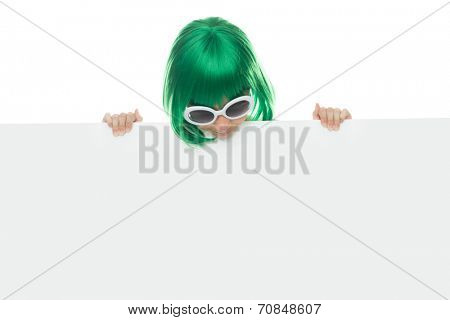 Cute young girl in a green wig and stylish sunglasses holding a blank white sign with copyspace for your text or advertising