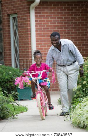 Smiling African American Man Helping Little Girl Biking Outdoor, grandpa and grand daughter in front of house