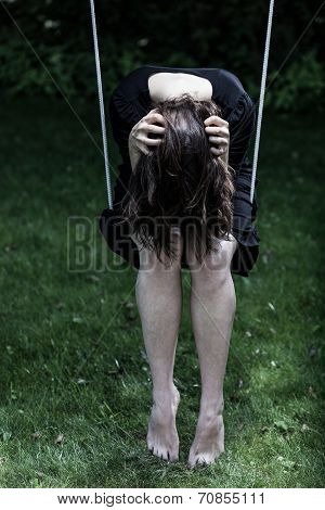 Depressed woman sitting on the swing holding her head poster