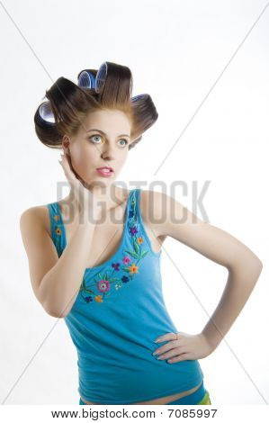 Young Beautiful Woman In Blue Shirt Is Getting Her Hairstyle Done With Curlers On Her Hair. Isolated