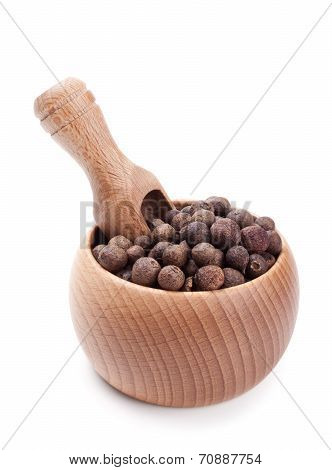 Wooden Scoop In Bowl Full Of Pimento Isolated On White