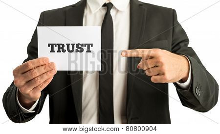 Business Man Holding A White Card Saying Trust