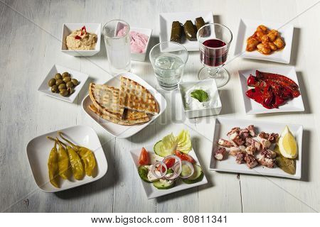variety of greek appetizers on white wood poster