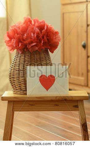 Vase basket with red pom pom tissue paper flower and a love letter in a room