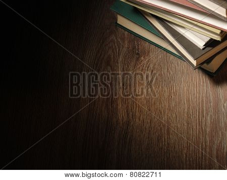 Pile of hardcover books stacked on top of one another in a shadowy room on a wooden desk with copyspace in the foreground