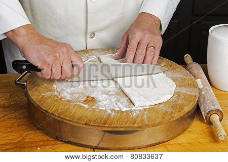 Slicing flattened dough into quarters