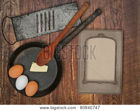 vintage utensils set, skillet,spoon,grater, eggs,butter, space for your text on a blank menu card