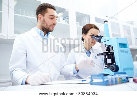science, chemistry, technology, biology and people concept - young scientists with microscope making test or research in clinical laboratory and taking notes poster