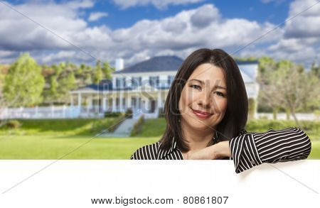 Pretty Hispanic Woman Leaning on White in Front of Beautiful House.