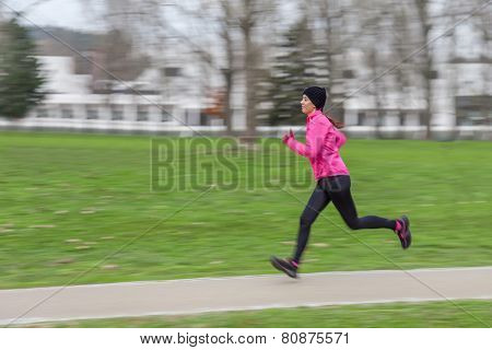 Young woman running on a cold winter day in an urban park with a panning effect.