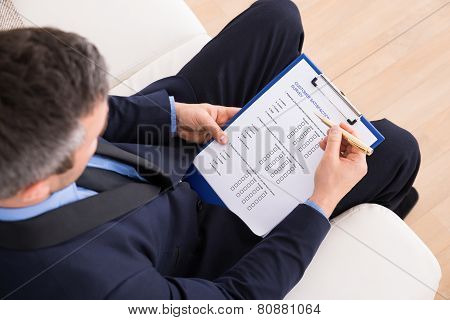 High Angle View Of Businessman Sitting On Couch Filling Customer Survey Form poster