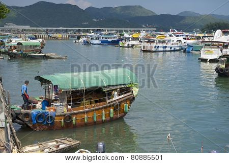 Man enters fishing boat, Sing Kee harbor, Hong Kong, China.