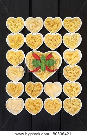 Pasta food selection in heart shaped porcelain dishes with basil herb and red chilli pepper over dark wood background. poster