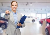 auto business, car sale, gesture and people concept - happy businesswoman or saleswoman with folder giving car key over auto show background poster