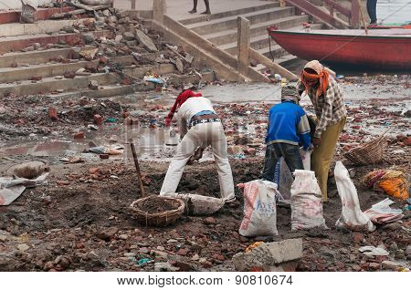 Indian Workers On The Banks Of Ganges River In Varanasi