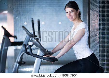 Woman riding an exercise bike in gym.Doing sport biking in the gym for fitness.Cardio and fat loss