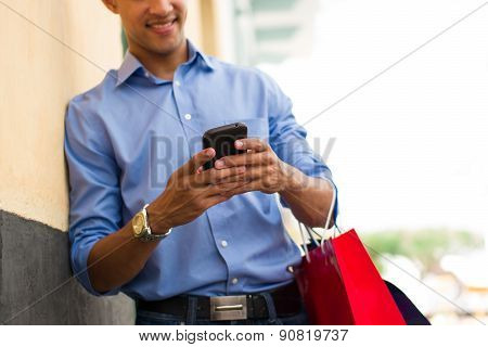 African American Man Writing Message On Phone Shopping Bags