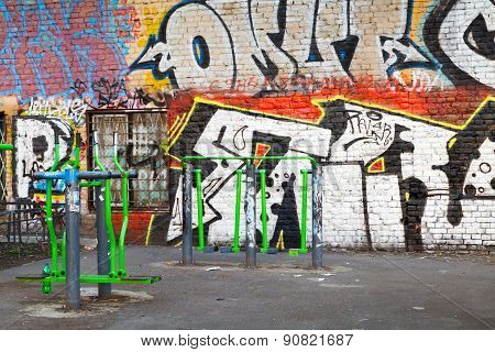Playground With Fitness Equipment And Chaotic Graffiti