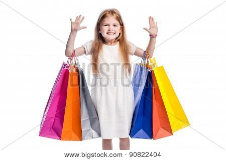 Smiling Girl With Hands Up And Big Colourful Shopping Bags.