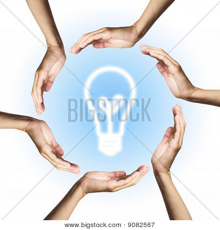 Glowing lightbulb surrounded by hands