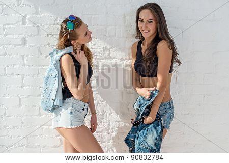 two pretty happy female friends in summer jeanswear street urban casual style talking, laughing havi
