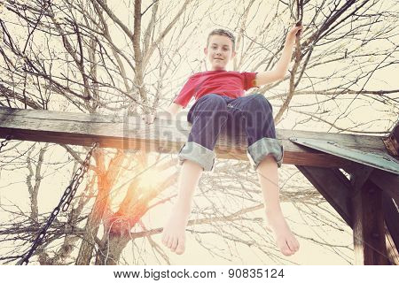 Adolescent boy sitting on top of a playground swing set.